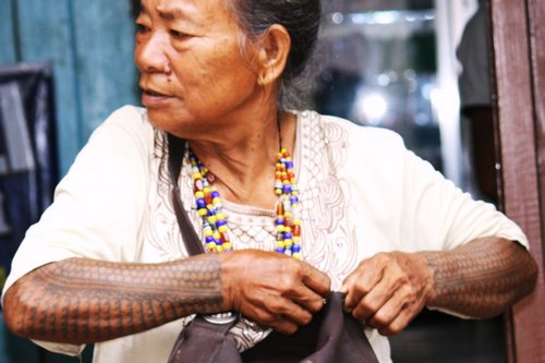 Woman from Tinglayan selling beads – native tattoos on forearms.